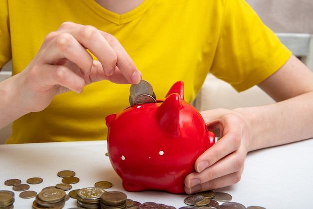Ręka kobiety umieścić monety pieniędzy w czerwonej skarbonce, aby zaoszczędzić pieniądze, kilka monet na stole. pojęcie gospodarki finansowej, kryzys