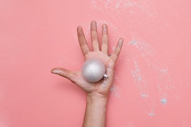 Ręka kobiety w blasku. ręcznie wykonane bombki choinkowe. majsterkowanie.