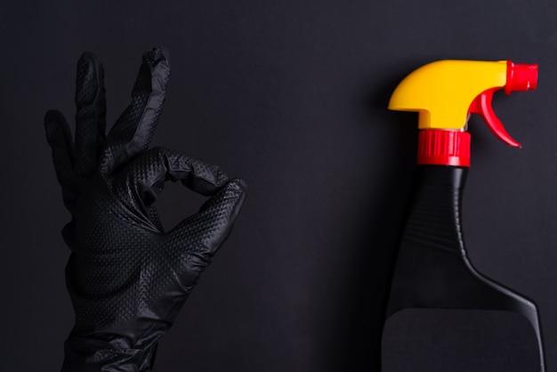 Ręka kobiety w czarnej lateksowej rękawicy do czyszczenia, wykonująca znak ok i plastikowa butelka z rozpylaczem na tym samym kolorze tła.