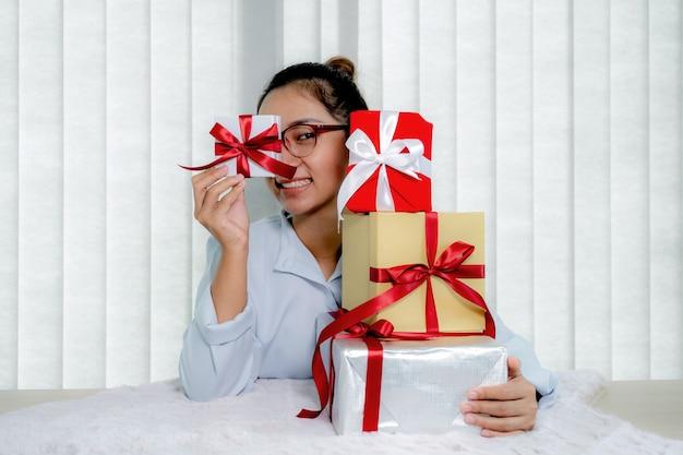 Ręka kobiety w niebieskiej koszuli trzymająca białe pudełko przewiązane czerwoną wstążką zasłaniającą oczy, prezent na święto specjalnych dni świątecznych, takich jak boże narodzenie, walentynki.