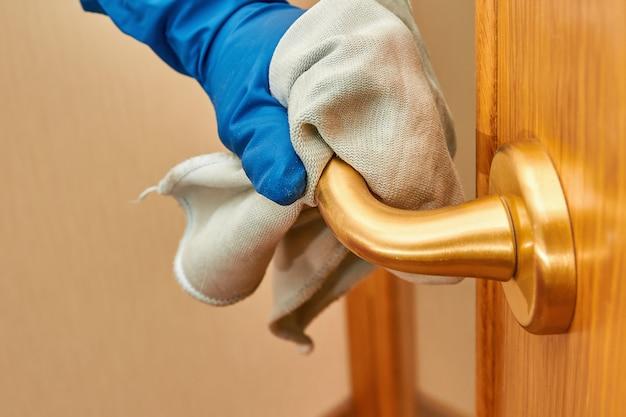 Ręka kobiety w niebieskiej rękawicy ochronnej przy użyciu środka dezynfekującego i ściereczki do czyszczenia klamki z wirusów. zbliżenie, selektywne focus