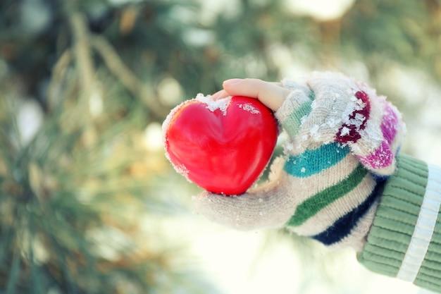 Ręka kobiety w rękawiczce z dzianiny trzymającej czerwone serce na zimowej powierzchni