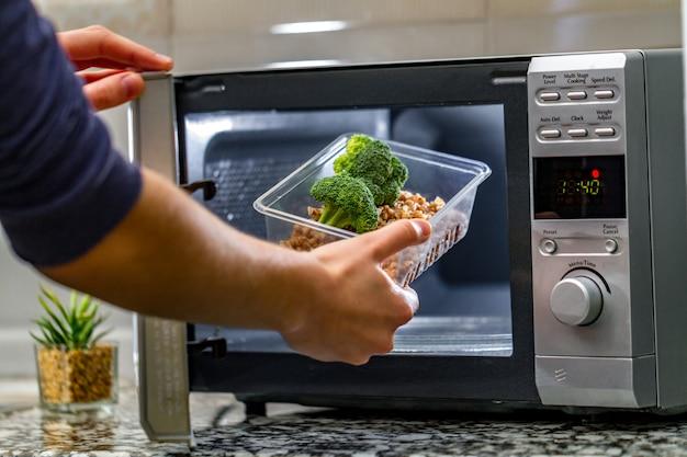 Ręka kobiety wkłada do kuchenki mikrofalowej plastikowy pojemnik z brokułami i kaszą gryczaną