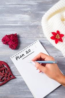 Ręka kobiety writing na notepad bożenarodzeniowych powitaniach z dekoracją na drewnianym
