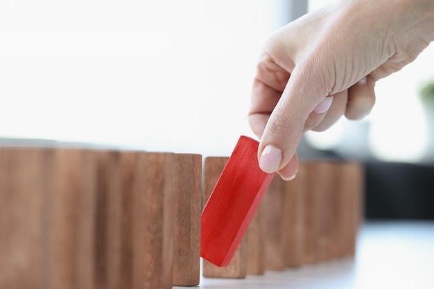 Ręka kobiety wyjmuje czerwony drewniany prostokąt. indywidualne podejście do rozwiązywania problemów biznesowych