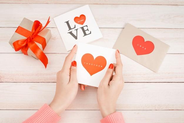 Ręka kobiety z czerwonym paznokciem trzymać list miłosny.