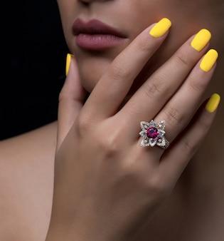 Ręka kobiety z diamentowym pierścionkiem w kształcie kwiatu z białym i bordowym kamieniem