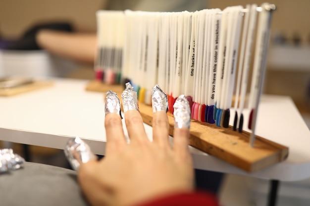 Ręka kobiety z folią na paznokciach stoi obok próbek lakieru z paletą kolorów.