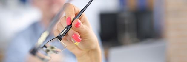 Ręka kobiety z jasnymi paznokciami trzyma okulary