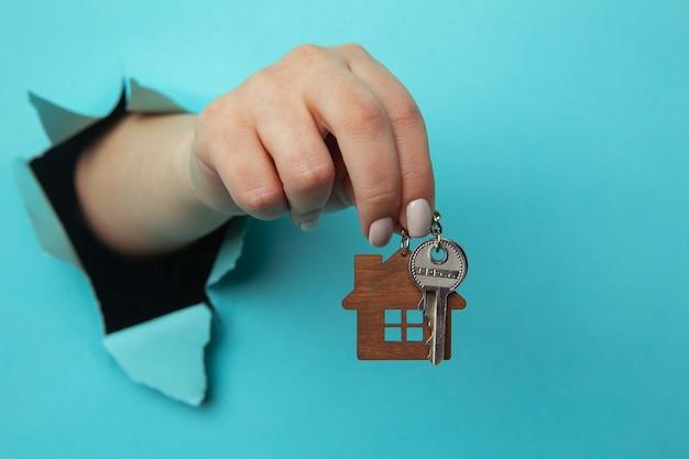 Ręka kobiety z kluczami od domu przez otwór w niebieskim papierze z bliska. koncepcja sprzedaży i wynajmu domu