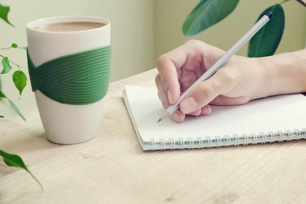 Ręka kobiety z ołówkiem zapisana jest w pamiętniku ze spiralami. obok stołu stoi filiżanka kawy i kwiaty z zielonymi liśćmi. widok z boku