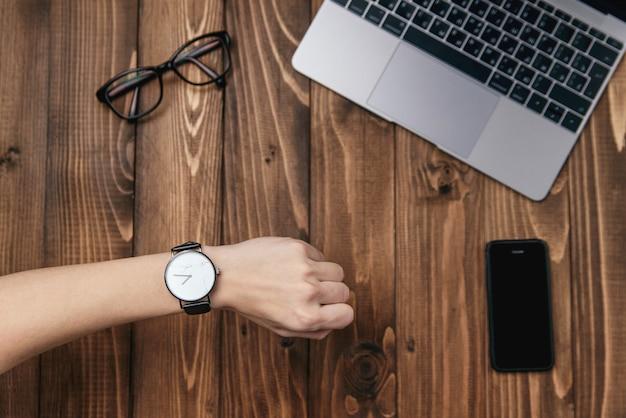Ręka kobiety z zegarkiem. widok z góry materiałów biurowych dla biznesu. laptop, telefon, okulary i zegarek na drewnianym stole. czas do pracy.