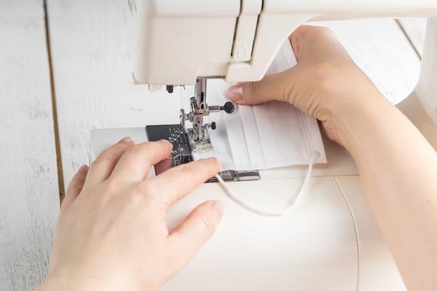 Ręka kobiety za pomocą maszyny do szycia, aby tkanina maseczki na twarz, ochrona zdrowia i koronawirus chroniły przy pomocy domowej szytej maski.