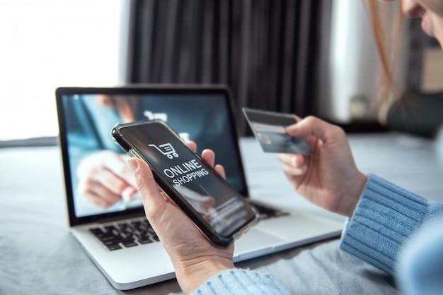 Ręka kobiety za pomocą smartfona i laptopa (