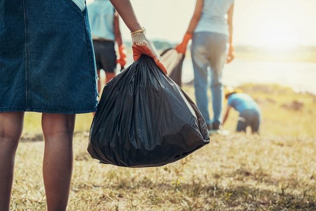 Ręka kobiety zbierając śmieci i ręka trzyma czarną torbę w parku