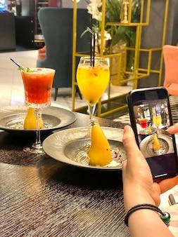 Ręka kobiety ze smartfonem fotografująca jedzenie w restauracji lub kawiarni