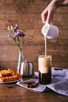 Ręka kobiety ze śmietanką wlewając mleko do szklanki z kawą