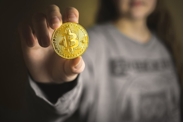 Ręka kobiety ze złotym bitcoinem, online wirtualnej przyszłości koncepcja waluty zdjęcie w tle