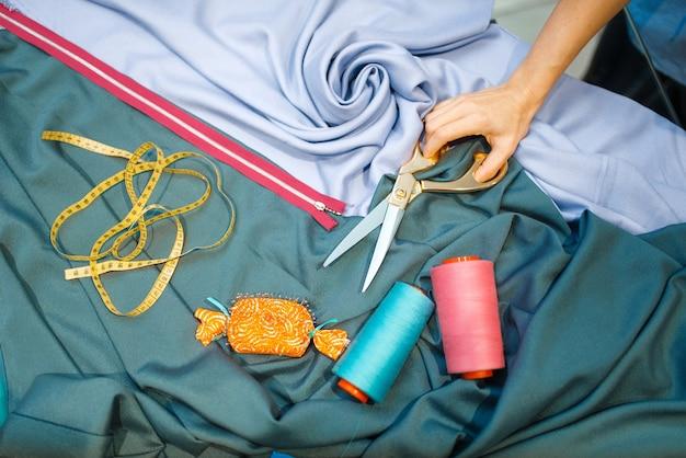 Ręka krawcowa z nożyczkami i tkaniną, widok z góry, warsztat tekstylny. kobieta pracuje z materiałem do szycia, krawcowa w miejscu pracy, krawiectwo