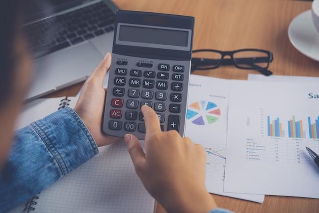 Ręka księgowego korzysta z kalkulatora. do analizy kosztów koncepcja kalkulacji zysków i strat oraz podatków przygotowanie sprawozdań finansowych