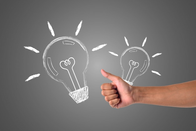 Ręka, która trzyma lampę, jest wysyłana do drugiej strony, zapisana białą kredą, rysuje koncept.