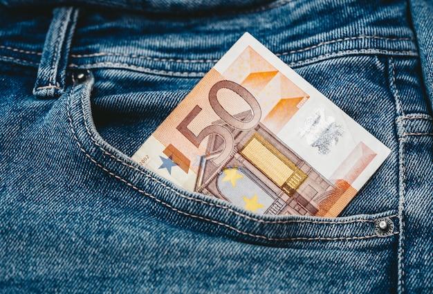 Ręka, która umieszcza banknoty euro w kieszeni dżinsów