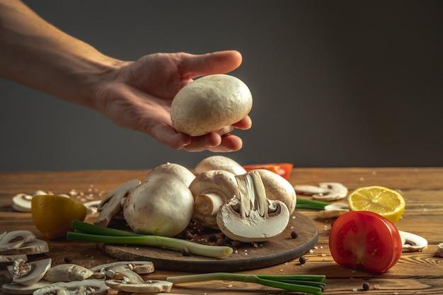 Ręka kucharza trzyma świeży grzyb nad drewnianym stołem z warzywami i innymi składnikami do gotowania potrawy