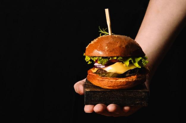 Ręka kucharzy serwująca świeży burger