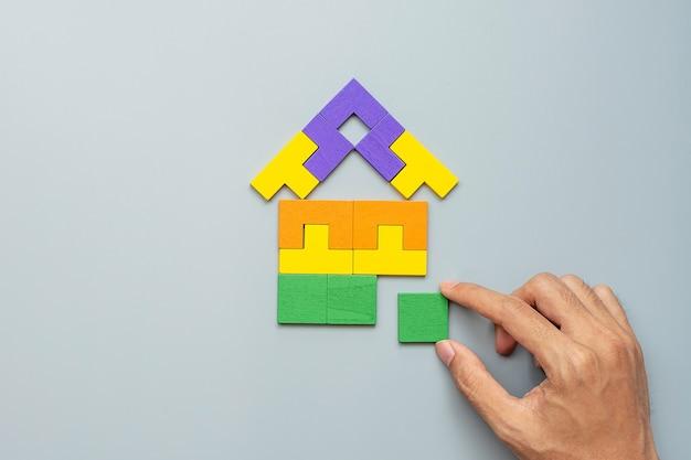 Ręka łącząca blok w kształcie domu z kolorowymi drewnianymi puzzlami na szaro. logiczne myślenie, logika biznesowa, rozwiązania, koncepcje racjonalne, dom, nieruchomości i strategie