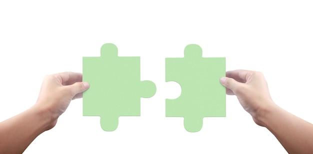 Ręka łączenia puzzli na białym tle