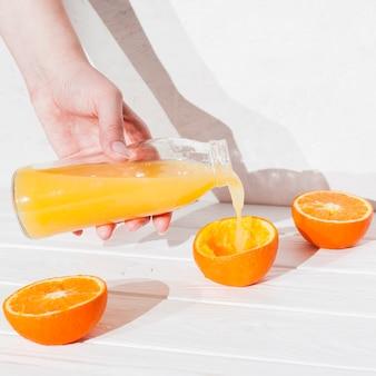 Ręka leje sok w wyciśniętej pomarańczy