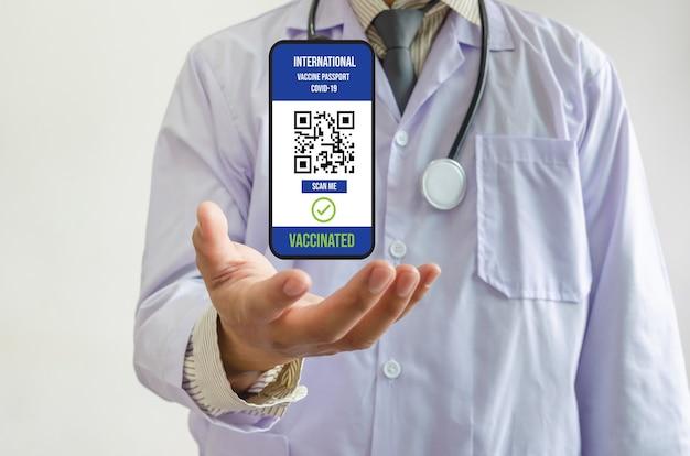 Ręka lekarza, międzynarodowa ikona telefonu komórkowego, paszport szczepionki przeciw covid, kod skanowania qr do podróży za granicę