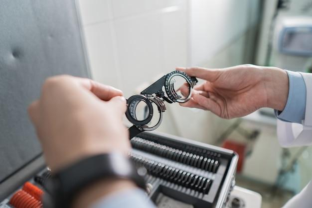 Ręka lekarza trzyma eksperymentalną oprawkę soczewki w pokoju w klinice okulistycznej na tle pudełka z oprawką okularów