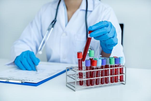 Ręka lekarza trzymająca probówkę z krwią i zapisuje wyniki badań i stosowanie leków pacjenta na wykresie, koncepcja badania lekarskiego.