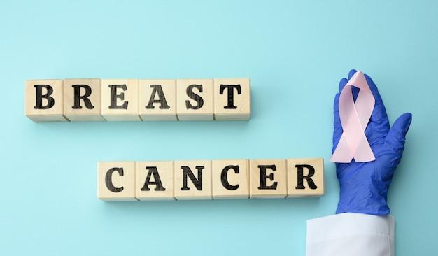 Ręka lekarza w niebieskiej rękawiczce trzyma różową wstążkę jako symbol walki z rakiem piersi oraz drewniane kostki z napisem na niebieskiej powierzchni