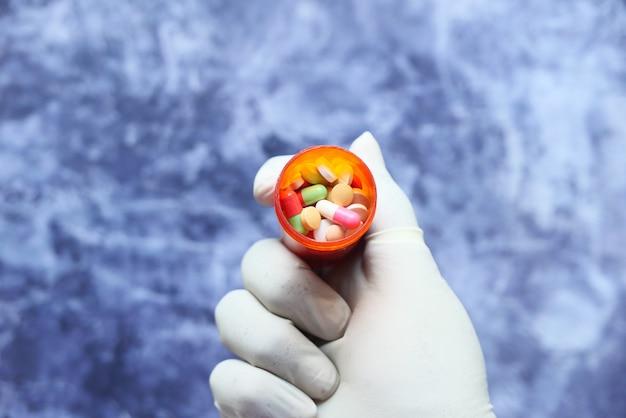Ręka lekarza w rękawicach ochronnych, trzymając pojemnik na pigułki