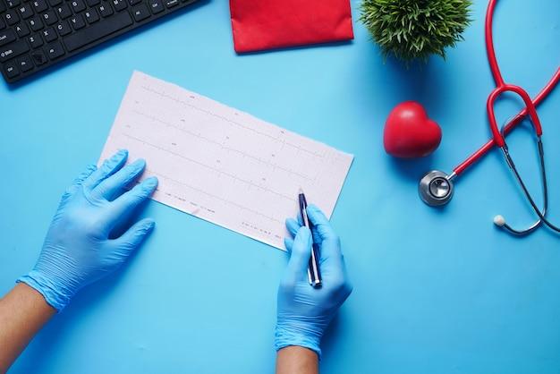 Ręka lekarza w rękawiczkach medycznych analizujących schemat cardio
