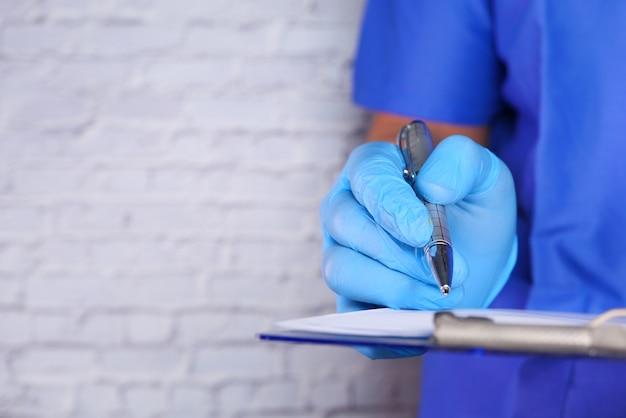 Ręka lekarza w rękawiczkach ochronnych wypisująca receptę,