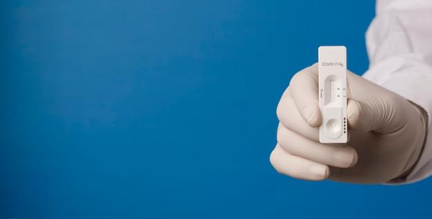 Ręka lekarza z szybkim testem na koronawirusa na niebieskim tle
