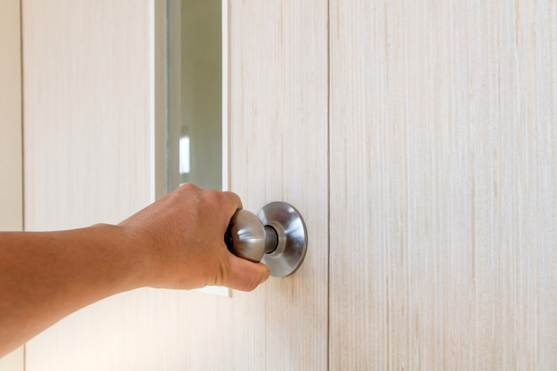 Ręka ludzi otwiera drzwi do środka, zewnętrzne drzwi otwierają się w drzwiach wejściowych