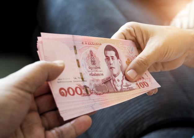 Ręka ludzi przekazuje pieniądze tajskiego bahta z tajlandii na rękę, która czeka na odbiór.