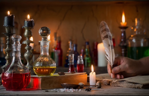 Ręka, magiczna mikstura, starożytne książki i świece