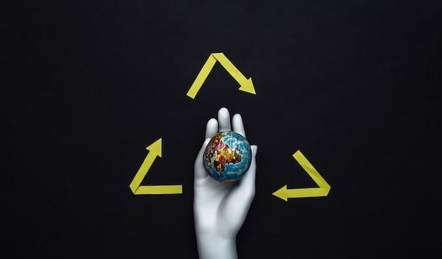 Ręka manekina biały trzymać globus i recyklingu strzałki znak na czarnym tle. ocal planetę!