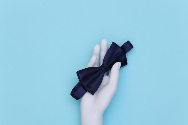 Ręka manekina trzyma muszkę na jasnoniebieskim tle. widok z góry