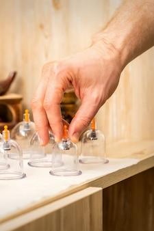 Ręka masażysty podnosi próżniowe szklane słoiki ze stołu w spa
