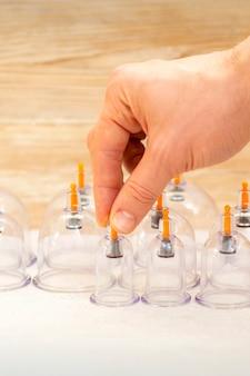 Ręka masażysty zdejmująca kubki próżniowe ze stołu przed bańkami