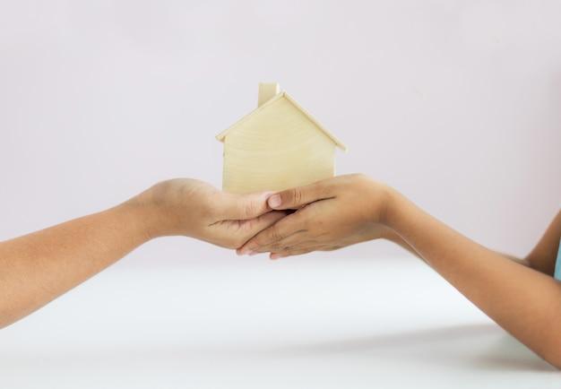 Ręka matki daje drewnianego domu modelowi córki metafory dziedzictwo nieruchomości pojęcie