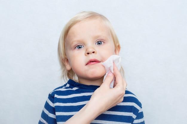 Ręka matki ociera twarz dziecka mokrymi chusteczkami na białym tle
