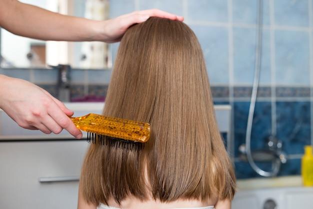Ręka matki ze szczotką czesanie długie jasne włosy cute girl dziecko po kąpieli