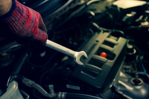 Ręka mechanika profesjonalisty trzymać klucza narzędzia z silnikiem samochodu